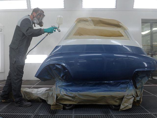 Hombre pintando un coche en el taller